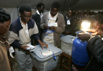 Zimbabwe election officials seal ballot boxes under gas light at end of polling day in Harare