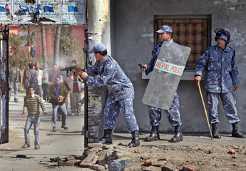 Nepali police officer fires teargas shell at students in the Patan Campus in Kathmandu