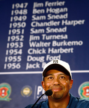 Tiger Woods listens to a reporter's question with a list of previous winners in the background in Medinah