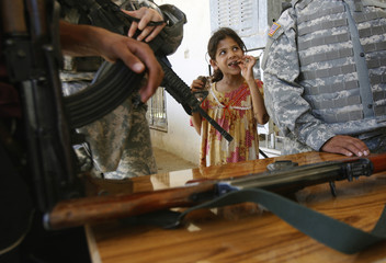 An Iraqi girl looks on as U.S. soldiers check weapons at the house of a local leader in a village near north Baghdad