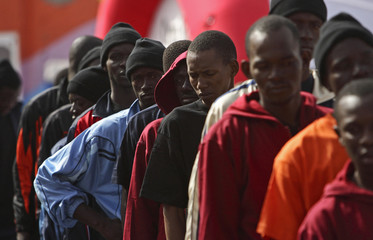 Would-be immigrants stand in line after arriving at the port of Los Cristianos on Spain's Canary island of Tenerife