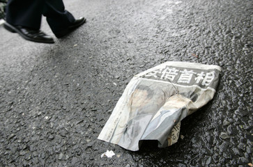 A pedestrian passes a crumpled special edition paper reporting Japanese Prime Minister Shinzo Abe's decision that he would resign in Tokyo
