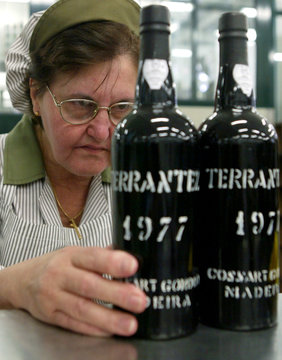 -PHOTO TAKEN 13OCT04- A worker checks the filling levels of bottles of vintage Madeira wine at the M..