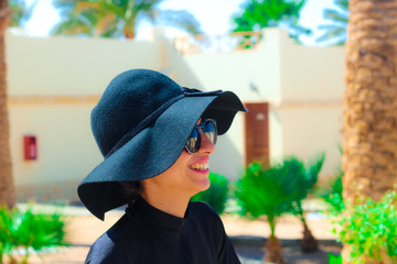 The Lady with the Black hat Laughing and having fun under the sun / The Lady in black with the Black hat having fun under the sun in the garden