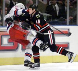 RANGERS KLOUCEK CHECKED BY BLACKHAWKS MCAMMOND IN NHL GAME.