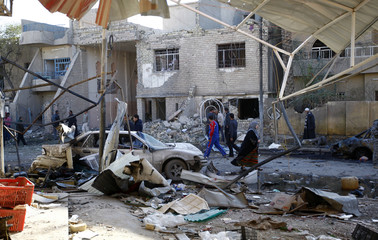 Residents gather at the site of bomb attacks in Baghdad's Nahdha neighbourhood