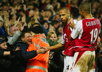 ARSENAL'S HENRY IS CONGRATULATED BY TEAM MATE GILBERTO AS HE SHAKESHANDS WITH FANS AT HIGHBURY.