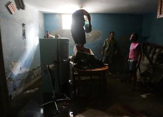 Cubans clean their basement apartment near Havana's seafront boulevard El Malecon