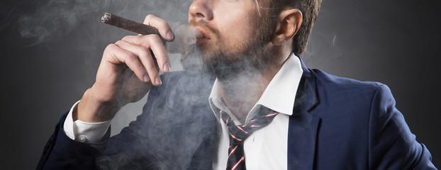 Closeup cigar smoking by bearded man wearing suit