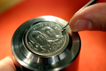 MINT WORKER PUTS LAST TOUCHES ON A COIN MOLD IN MADRID.