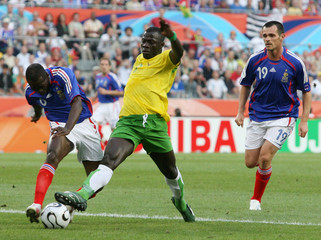 France's Makelele battles for the ball with Togo's Salifou in front of France's Sagnol during their Group G World Cup 2006 soccer match in Cologne