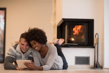multiethnic couple using tablet computer on the floor