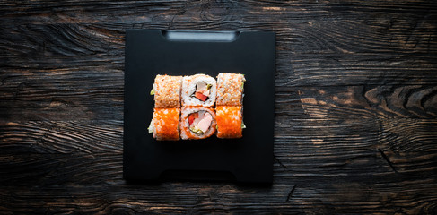 set of sushi with caviar and sesame on black tray and wooden background top view