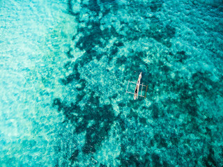 lonely african boat in clear turquoise ocean, top view
