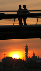 A couple are silhouetted above the London skyline and the BT Tower as they cross the Millennium Bridge at sunset in London