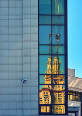 Reflections of the main building of Moscow State University in windows of its fundamental library in the spring campus under blue sky.