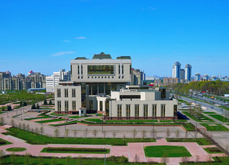 A modern building of the fundamental library in spring campus of Lomonosov Moscow State University under blue sunny sky.