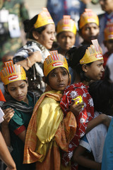 Children wait in line to place flowers at the altar of the Shahid Minar in Dhaka