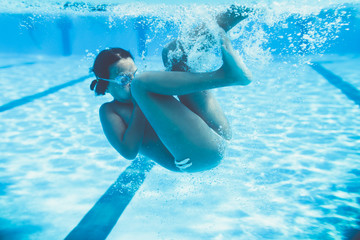 Underwater fun. Cute little girl with goggles swimming underwater and diving in the swimming poll. Sport and leisure.
