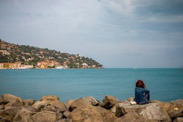 Femme sur la digue du port de Porto Santo Stefano en Toscane