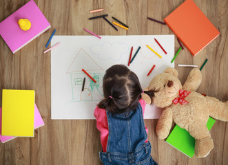 Little Asian girl drawing in paper on floor indoors, top view of child on floor