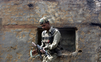 An Indian soldier hold his weapon as he searches  a house in Tral