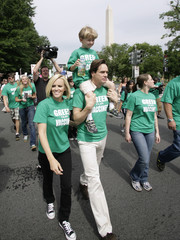 Actors Jenny McCarthy and Jim Carrey, carrying her son Evan, take part in a rally calling to eliminate toxins from children's vaccines near the Washington Monument