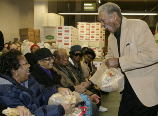 Actor Morgan Freeman hands out bags of food to senior citizens during an event at the Capital Area Food Bank in Washington