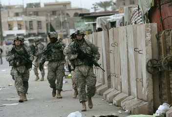 U.S. soldiers walk past a new concrete wall at a market in the southeast of Baghdad