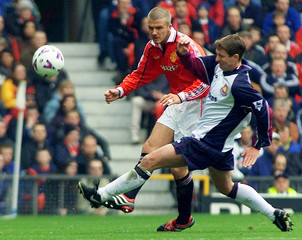 MANCHESTER'S BECKHAM IS TACKLED BY WEST HAM'S MONCUR AT OLD TRAFFORD.