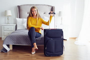 Happy woman with suitcase sitting on bed in hotel