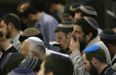 Israeli men pray as hundreds attend a memorial service for eight students in Jerusalem