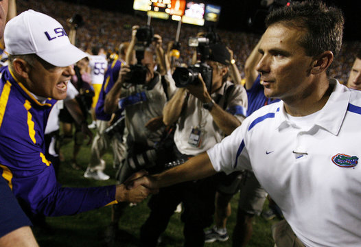 Louisiana State University head coach Miles shakes hands with University of Florida head coach Meyer in Baton Rouge