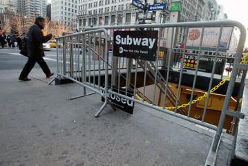 Pedestrian walks past closed subway station in New York