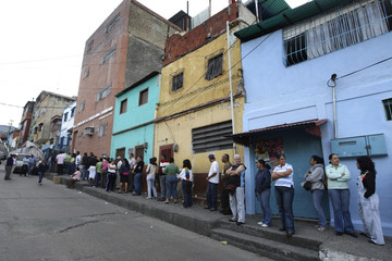 Venezuelans line up to vote during a referendum in Caracas