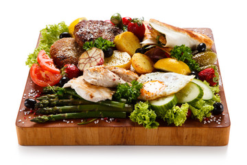 Various meat and vegetables served on cutting board