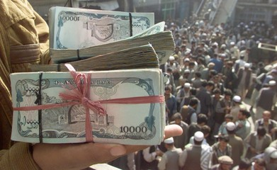 AN AFGHAN MAN HOLDS BUNDLE OF AFGHANIS AT THE MONEY CHANGER IN KABUL.