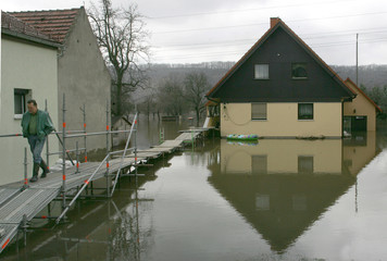 An unidentified resident leaves a flooded house as he walks on a self-made catwalk in Brockwitz