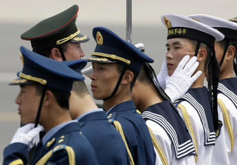 Military official adjusts posture of member of honor guard as they prepare for welcome ceremony for Japan's PM Aso at Beijing airport