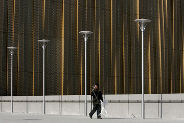Worker walks outside the Beijing Olympic Basketball Gymnasium in Beijing