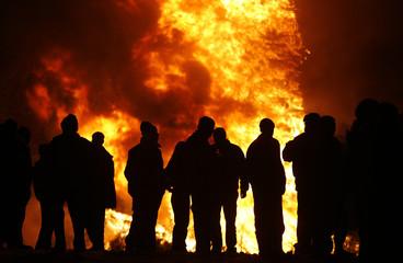 People gather near a bonfire during rituals in celebration of Sirni Zagovezni festival in the village of Dobrinishte