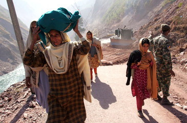 Kashmiri earthquake survivors walk on the Neelum Valley road, which was heavily damaged by the October 8 earthquake, in Khori, north of Muzaffarabad
