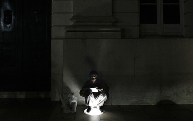 Man reads a newspaper as he sits on a light in downtown Lisbon