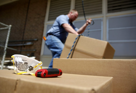 Worker hoists a box of air filters in Texas