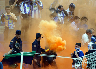 SPANISH RIOT POLICE CARRY SMOKE CANISTER IN MALAGA STADIUM DURINGMATCH.