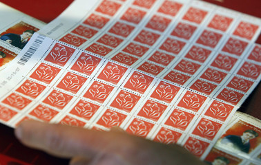 A customer purchases stamps at France's La Poste post office in Margaux
