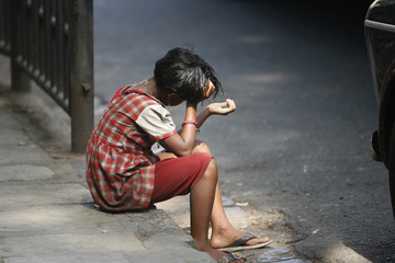 A girl sits on a pavement waiting to receive alms at a street in Mumbai