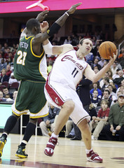 Cleveland Cavalier Zydrunas Illgauskas is fouled by Seattle SuperSonic Johan Petro in Cleveland