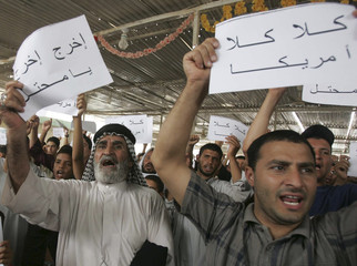 Demonstrators hold up signs during a protest in Kerbala