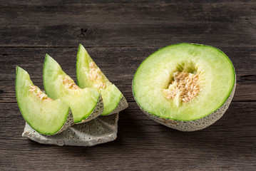 ripe and fresh melon, sliced and half on old wooden table